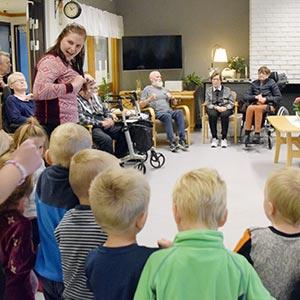Barnehagebarn synger for sykehjemsbeboere i storstuen