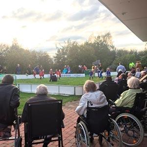 Sykehjemsbeboere i rullestol som ser på fotballkamp ute