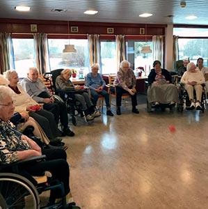 Eldre mennesker i rullestol spiller boccia sammen innendørs