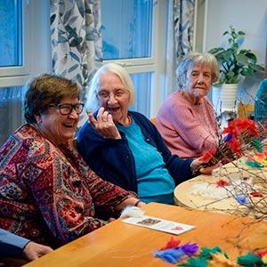 Tre eldre damer sitter ved et bord og ler sammen