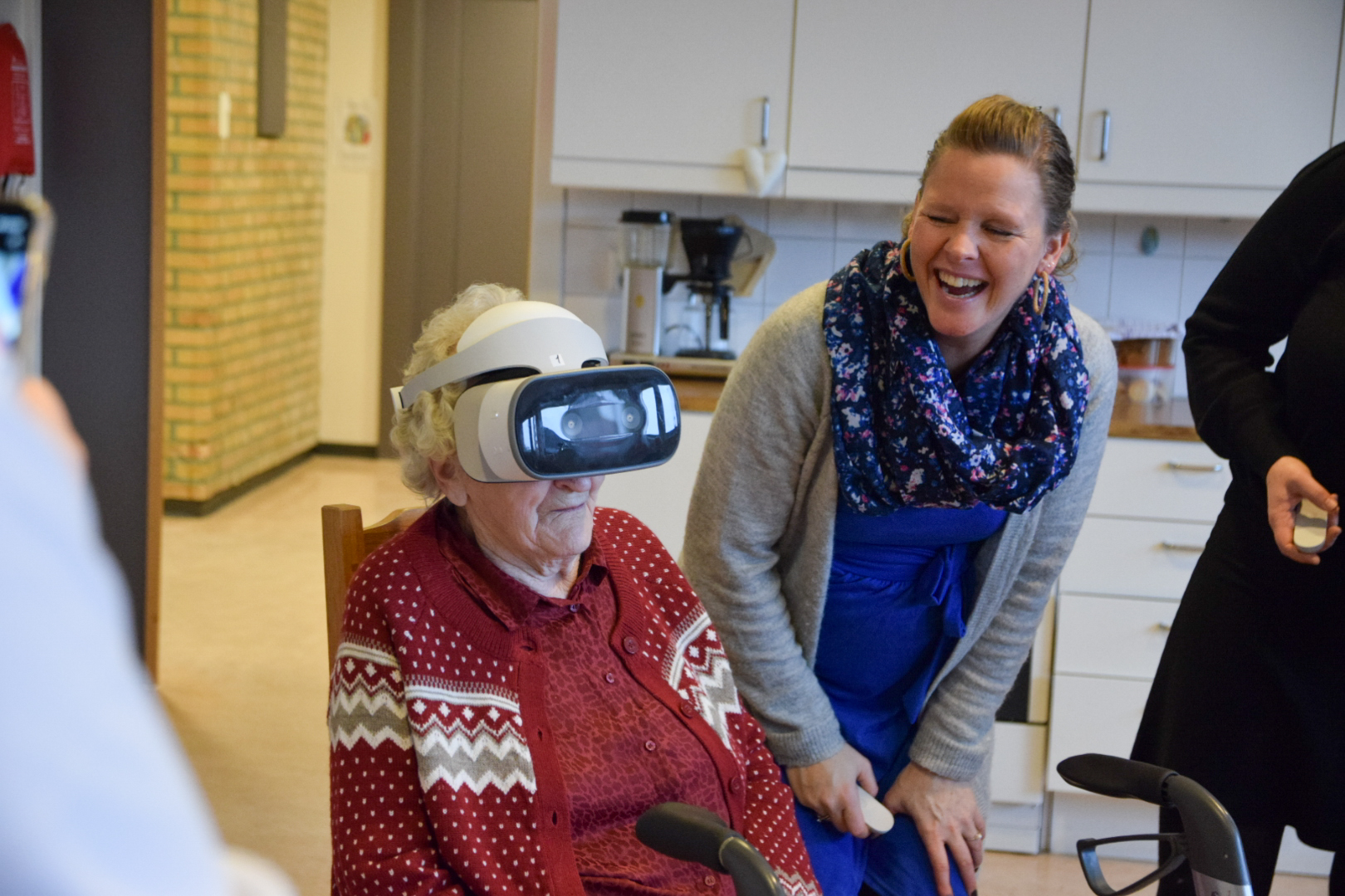 Eldre dame prøver VR-briler. Yngre dame står ved siden av og smiler.