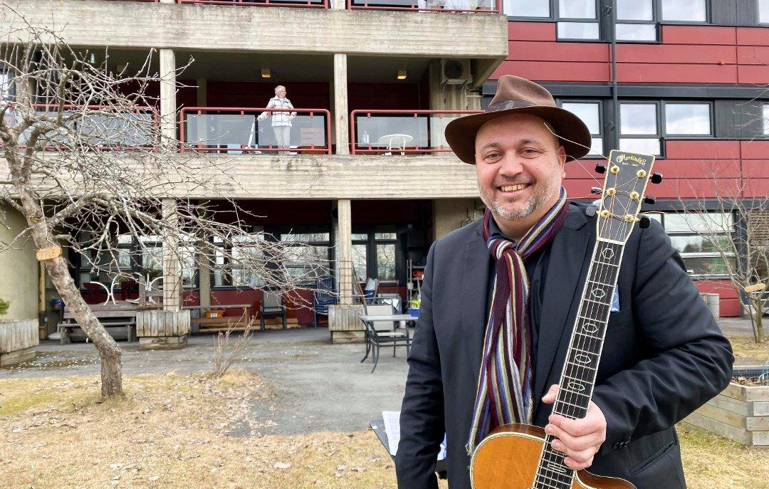 Bernt Torp står med gitar foran Brumunddal Sykehjem etter utendørskonsert