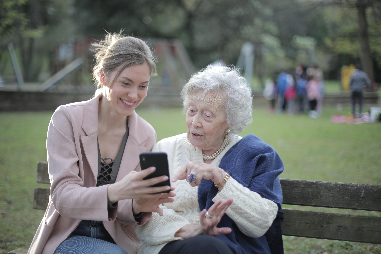 En smilende ung og eldre kvinner sitter på en benk i en park sammen og ser på en telefon