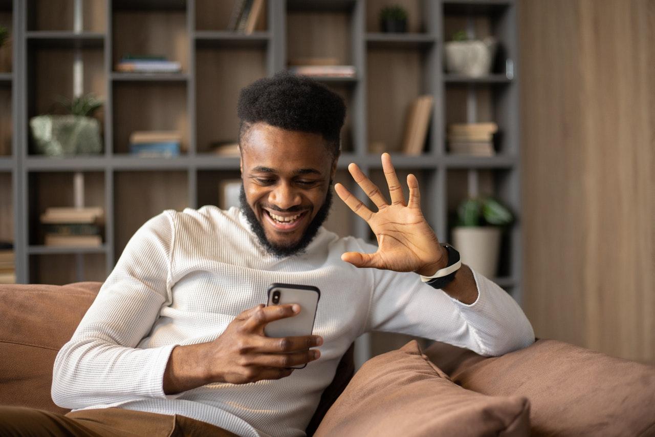 glad mann vinker i videosamtale til mobilkamera