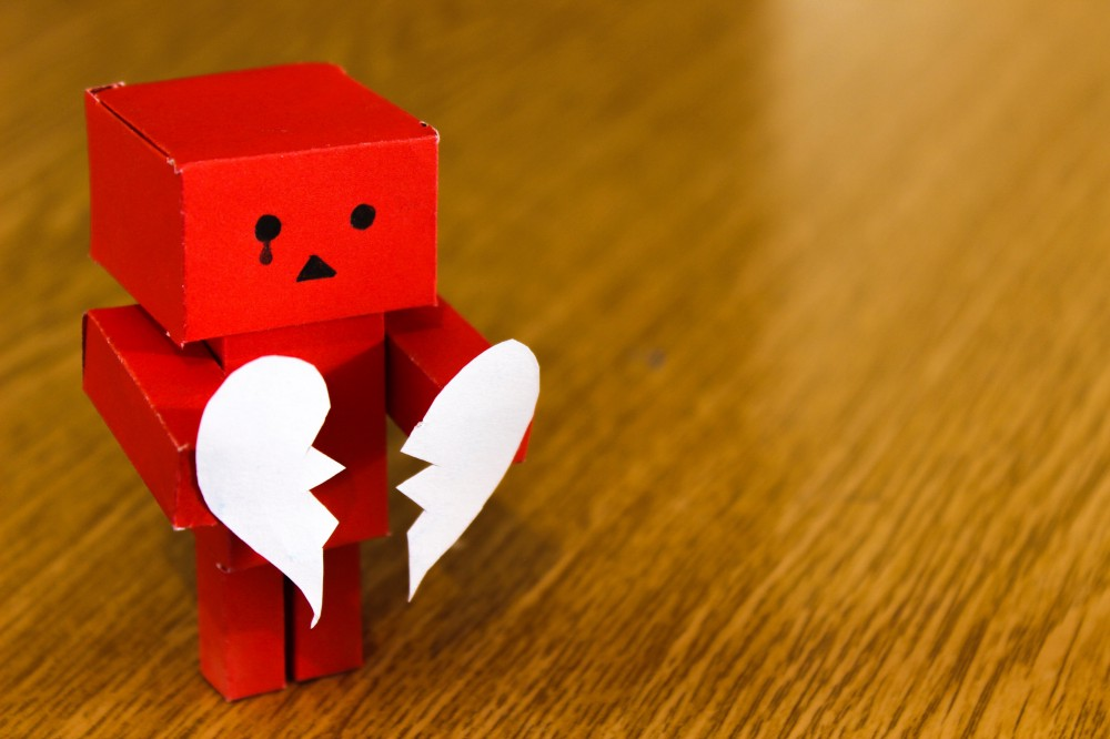 Cardboard model holding a broken paper heart