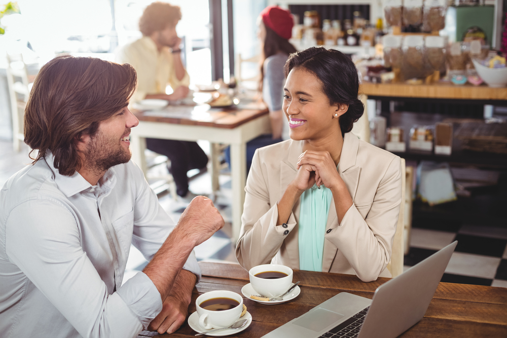 Smiling man and woman using a laptop while having cup of coffee in cafe