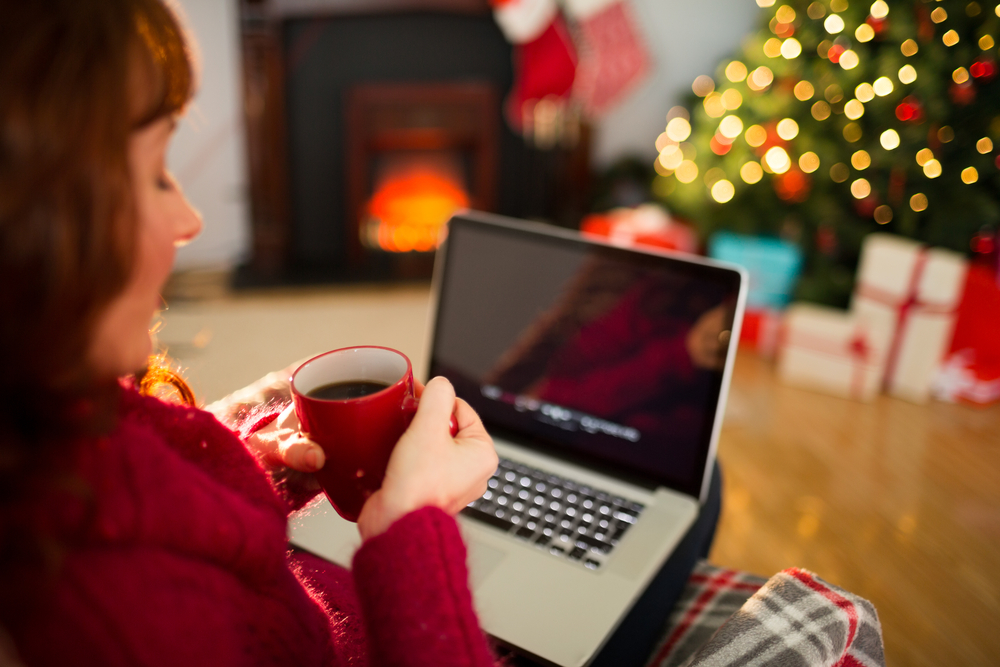 Redhead holding hot drink and using laptop at christmas in the living room