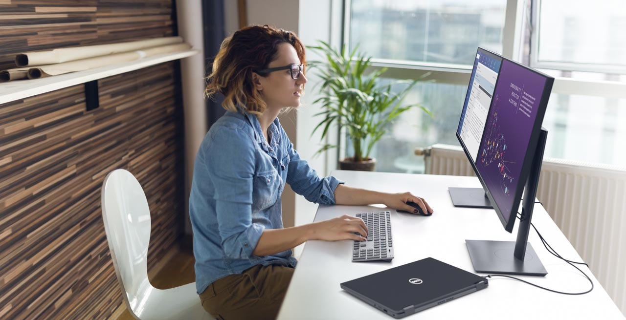 Female business owner working on her Dell Latitude computer at her home office.
