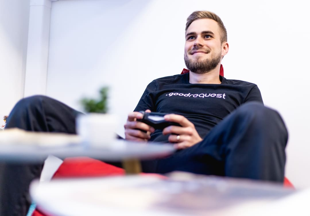 Roman Kralik leader of QA in goodrequest playing playstation