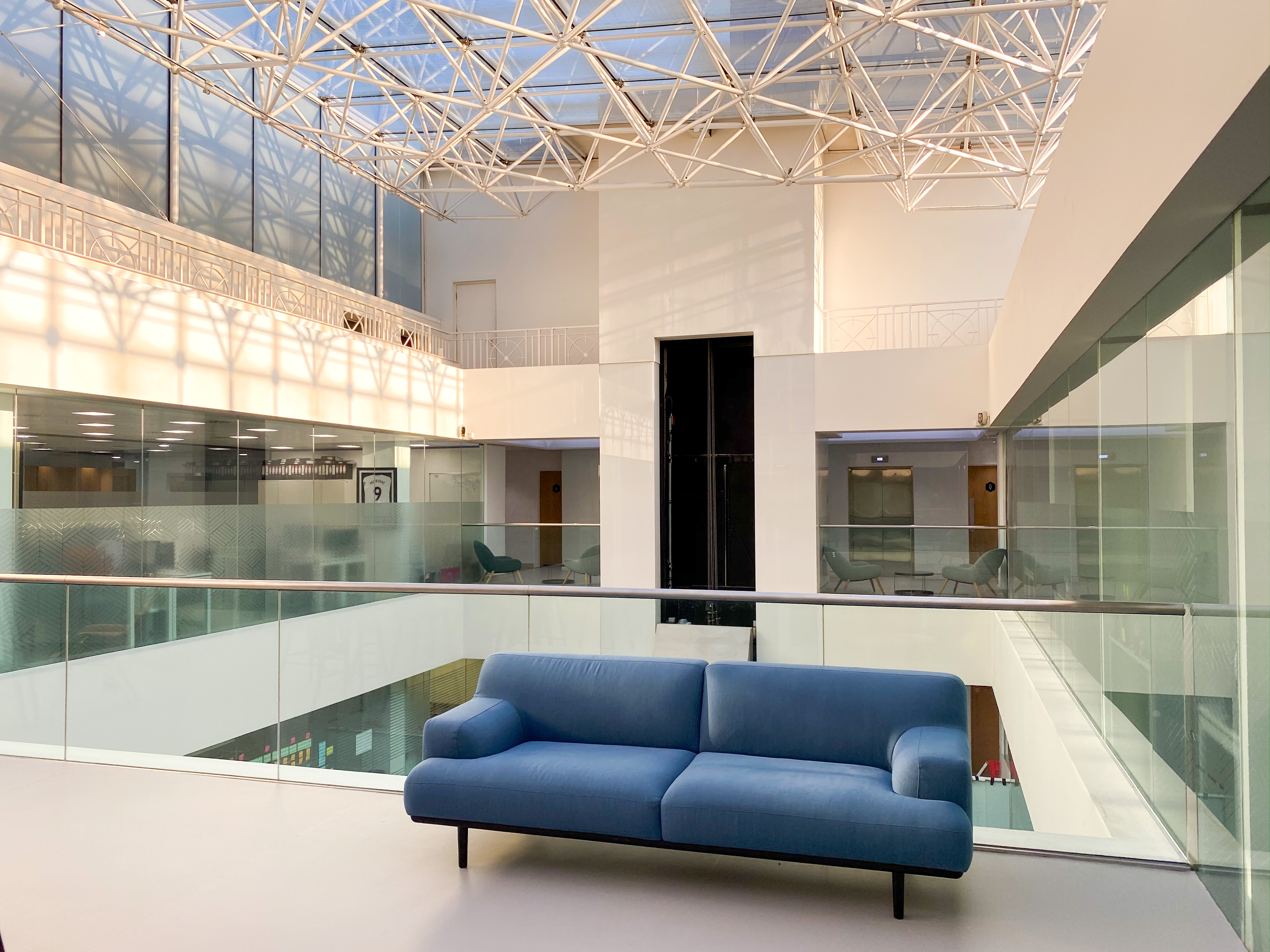 Photograph of the top floor of an open plan office with a large glass ceiling. Blue two seater fabric sofa in the foreground. Behind the chair in the background is an elevator with two blue arm chairs either side.