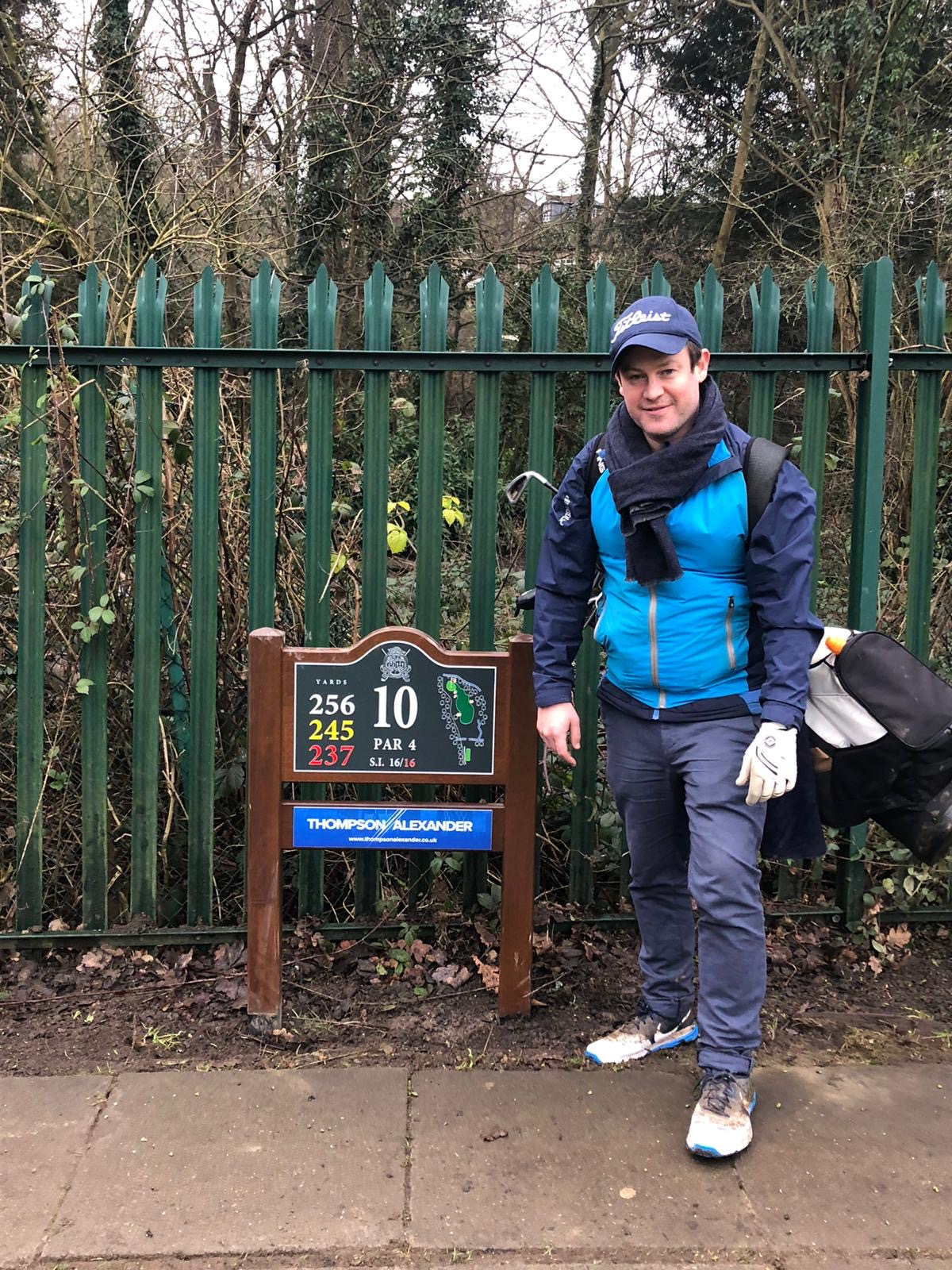 A photograph of Jamie at the 10th hole sign at Finchley Golf club, which is sponsored by Thompson Alexander. Green fence and trees in the background. Jamie is smiling and carrying his golf bag.