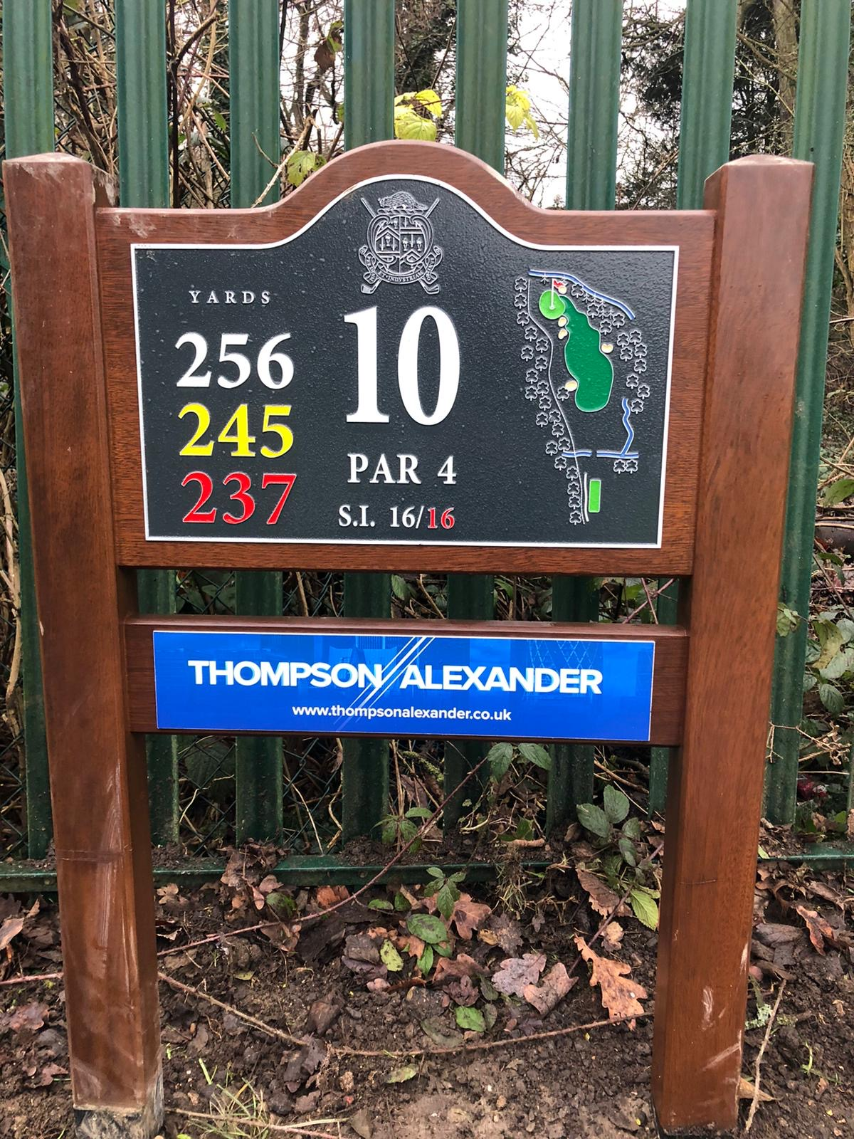 A close up of the 1oth hole sign at Finchley golf club. A dark brown sign with a black plaque and Thompson Alexander logo underneath.