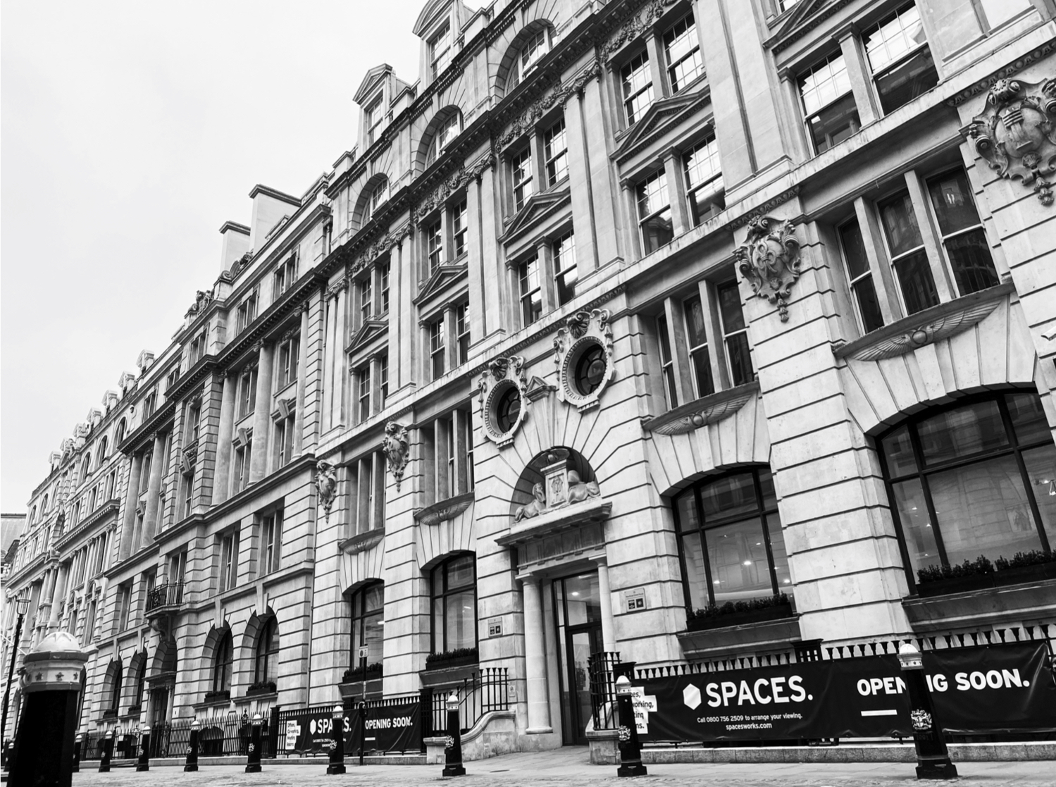 A black and white photograph of outside a brick building in central London. A Spaces banner on the railings in front of the building
