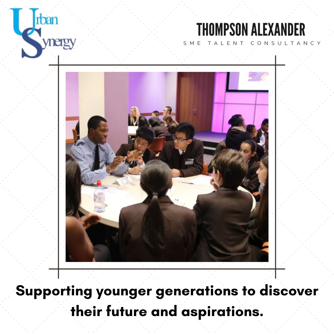 A group of students in uniform sat around a table whilst an adult mentor and role model speaks to them. A photograph taken at an Urban synergy in school mentoring event. Text at the bottom reads 'Supporting younger generations to discover their future and aspirations'.