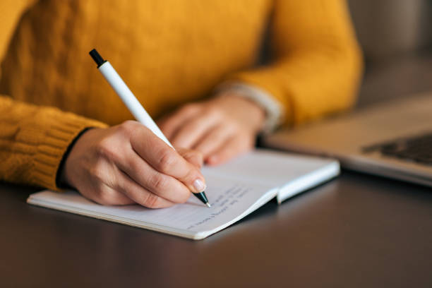 Image of a person sat at a brown wooden desk, next to a laptop and writing in a notebook. The person is wearing a yellow knitted jumper.