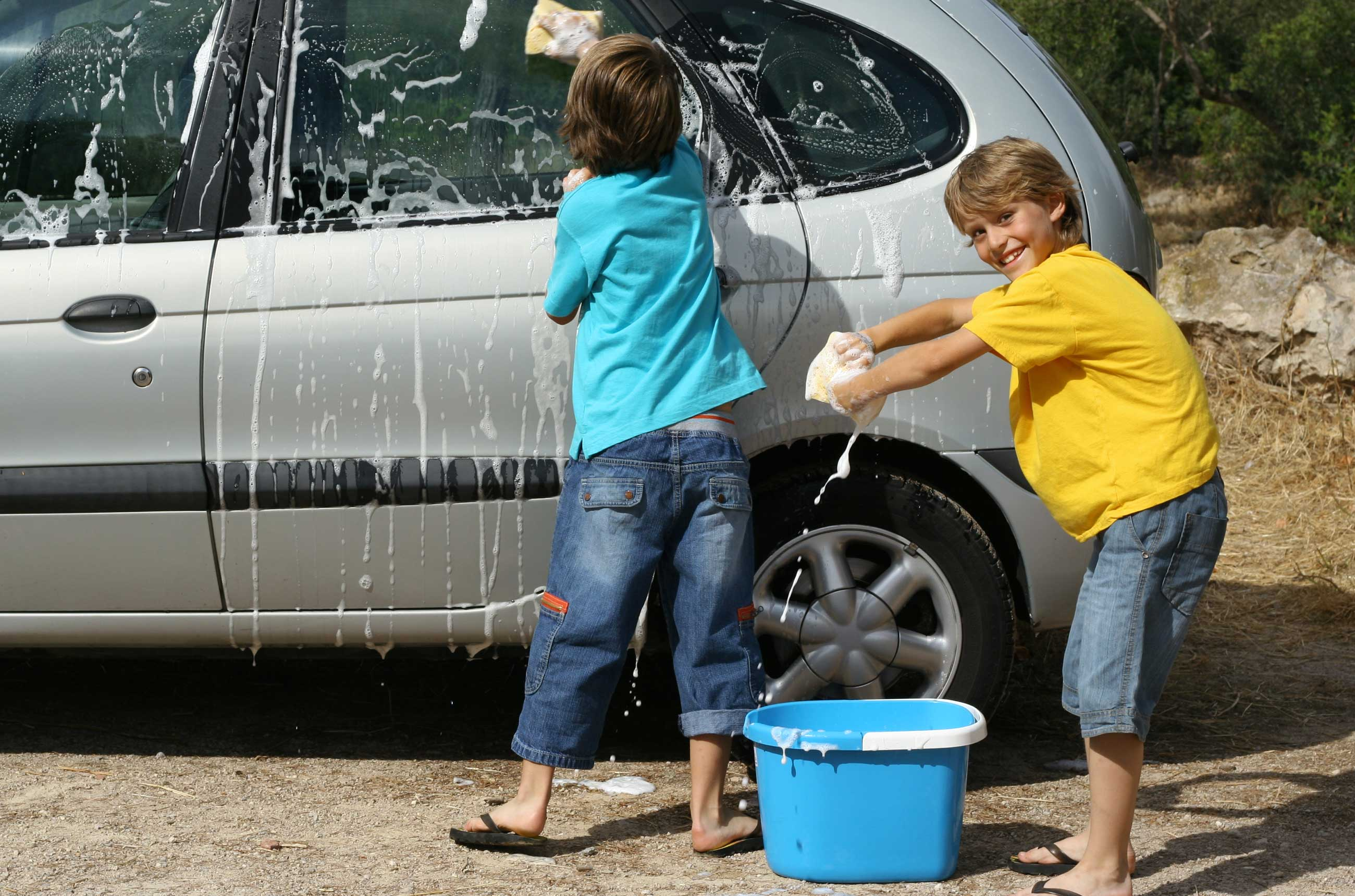 2 kids washing a car