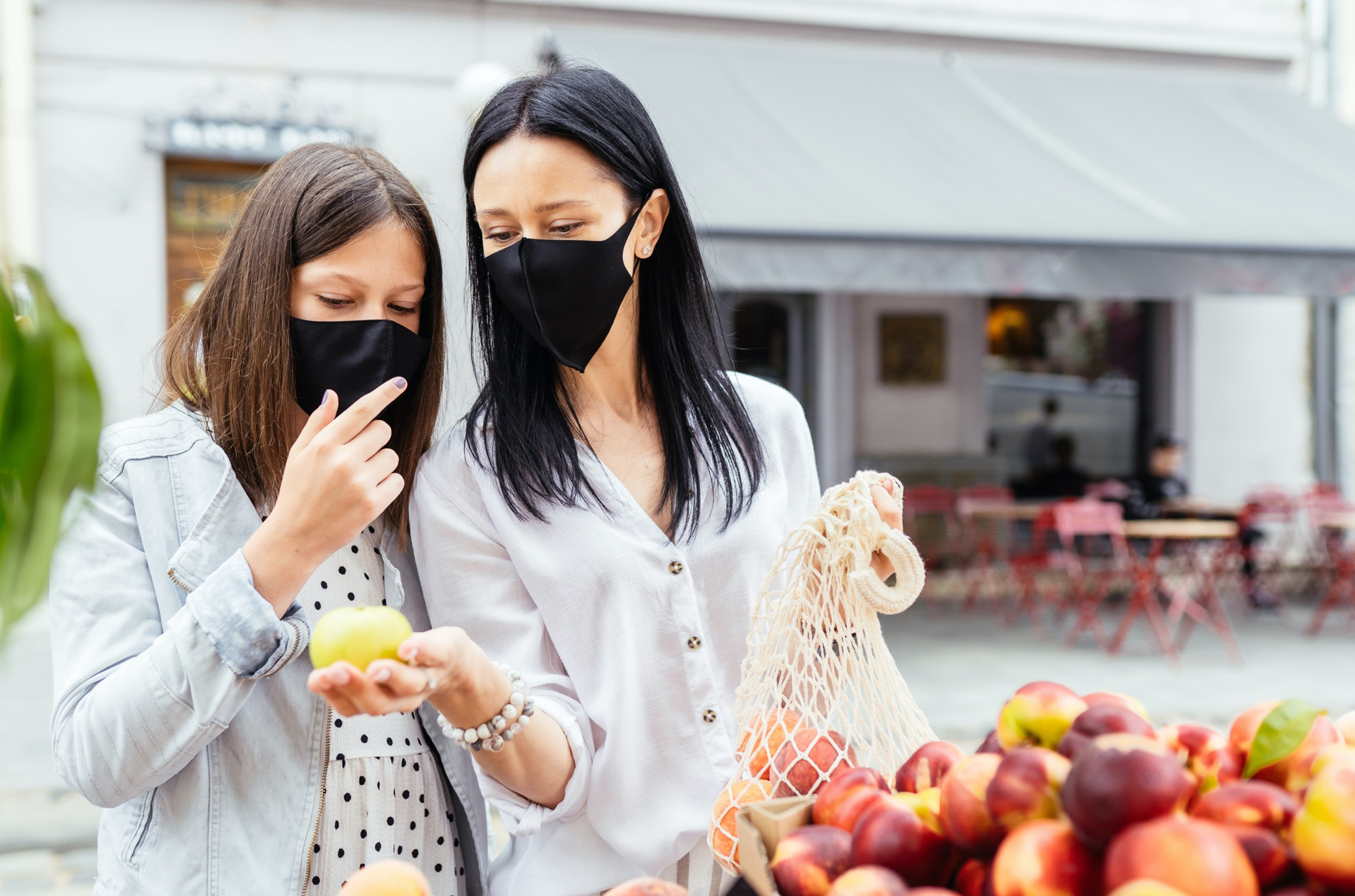 Two people wearing masks while shopping for fruit