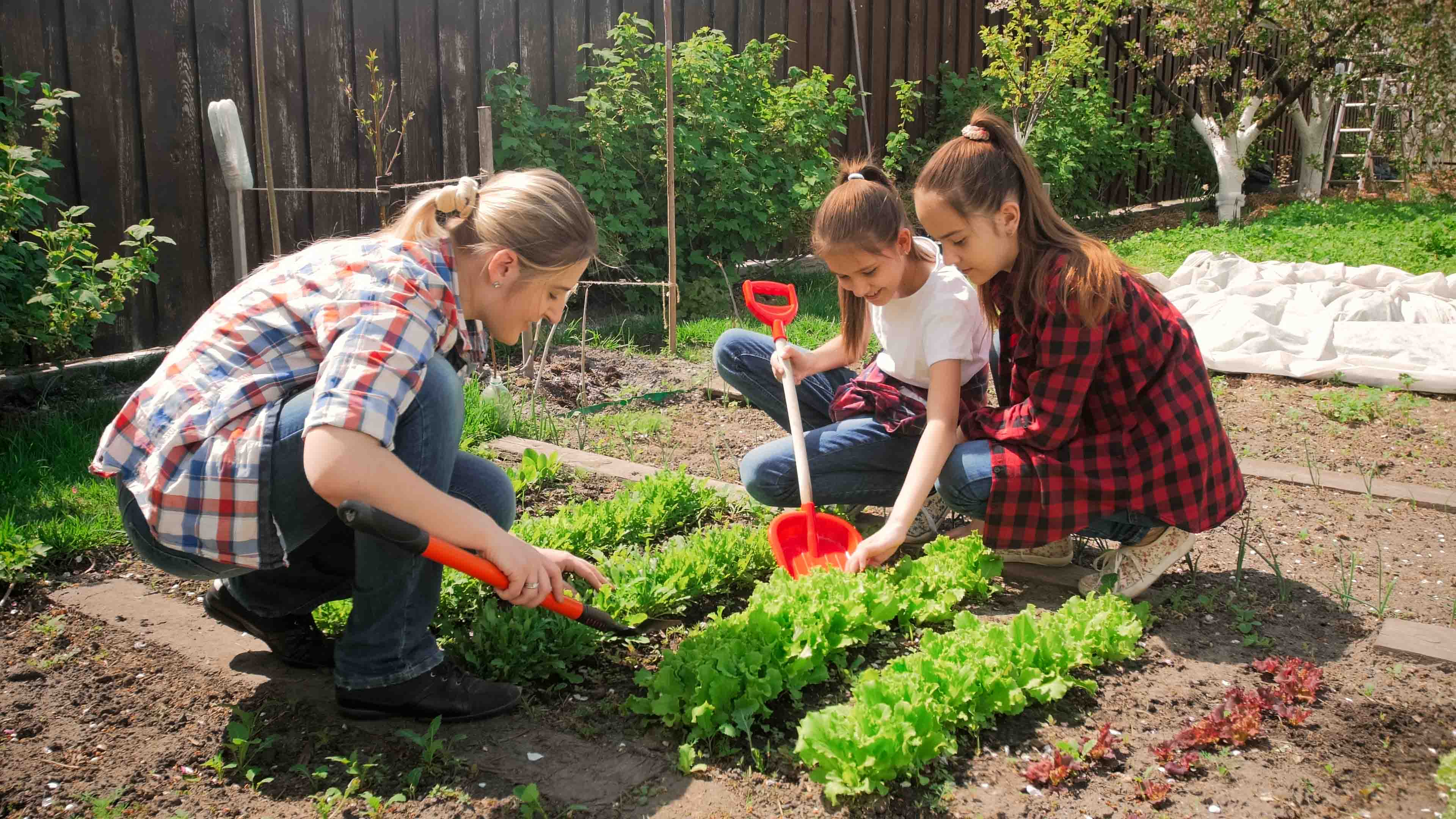 Kids helping their mother with gardening outside