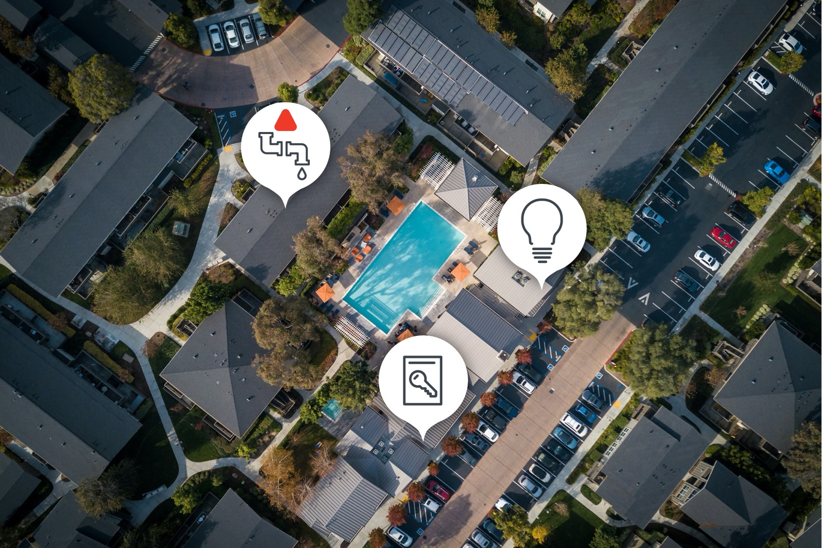 Aerial view of a low-rise multifamily community with a courtyard pool in the center