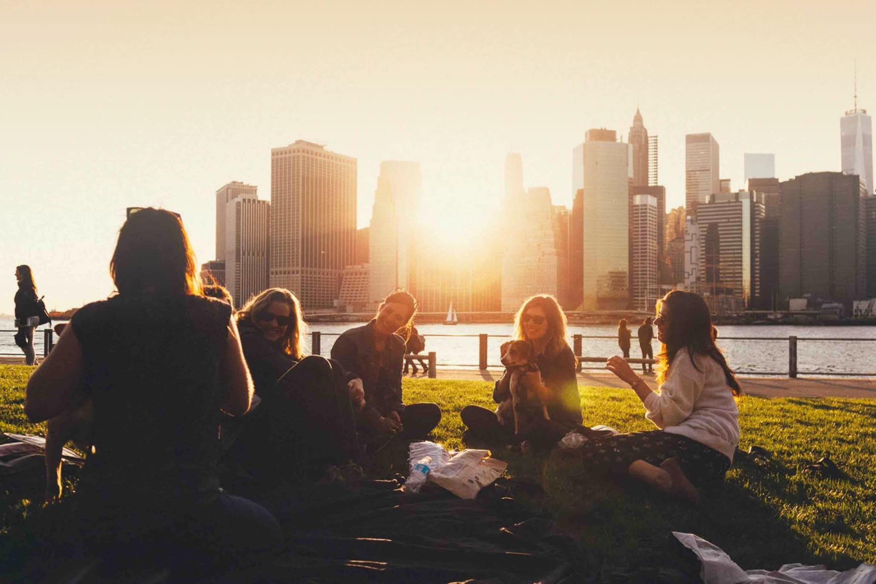 Group of neighbors from a high-rise community having a picnic at a riverfront park in the city