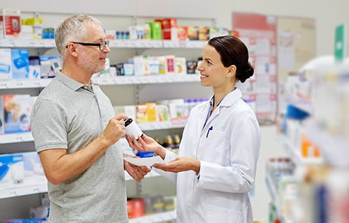 Man speaking with pharmacist in pharmacy