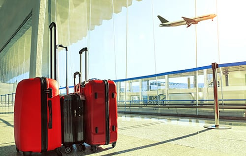 Image of red luggage in an airport lounge with a passenger jet taking off in the background