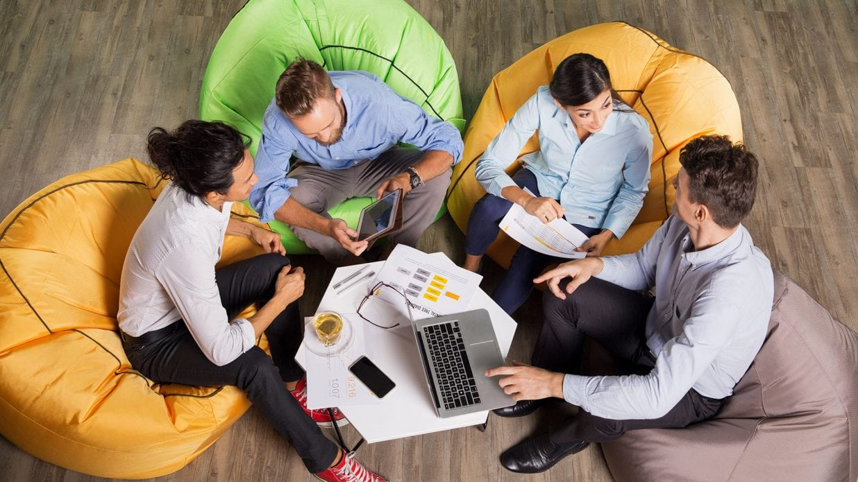 mage of a group of young professionals in casual dress working with a laptop and tablet sitting in bean bag chairs