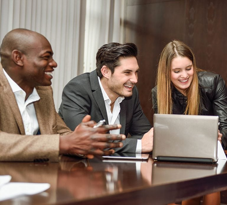 Two men and a woman smiling looking at a laptop