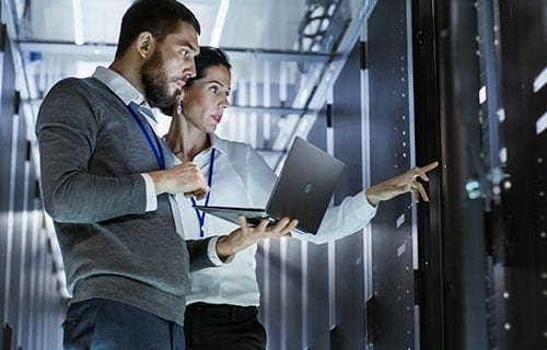 Man, and a woman in a server room looking at servers on server racks