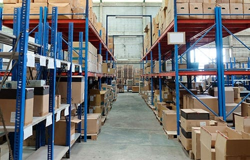 Image of rows of shelves with cardboard boxes in a warehouse