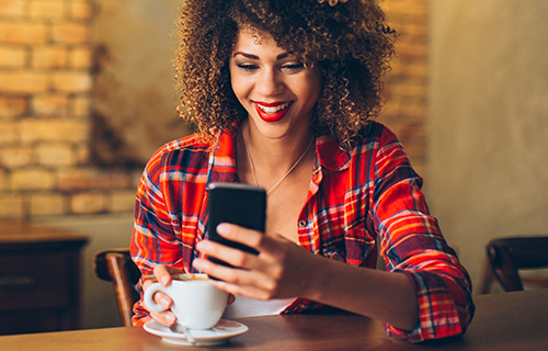 African American woman in plaid shirt looking at smartphone in a café with a latte
