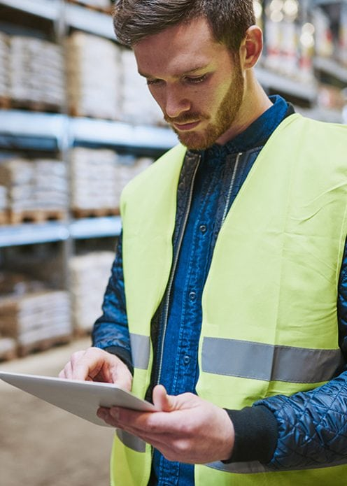 Man in a yellow vest in a warehouse looking at a tablet