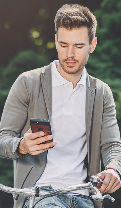 Man in grey cardigan on a bicycle looking at smartphone