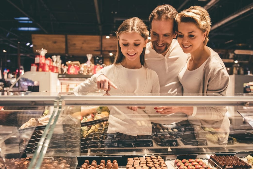 Family of man woman and girl picking out chocolates in a store from a glass display