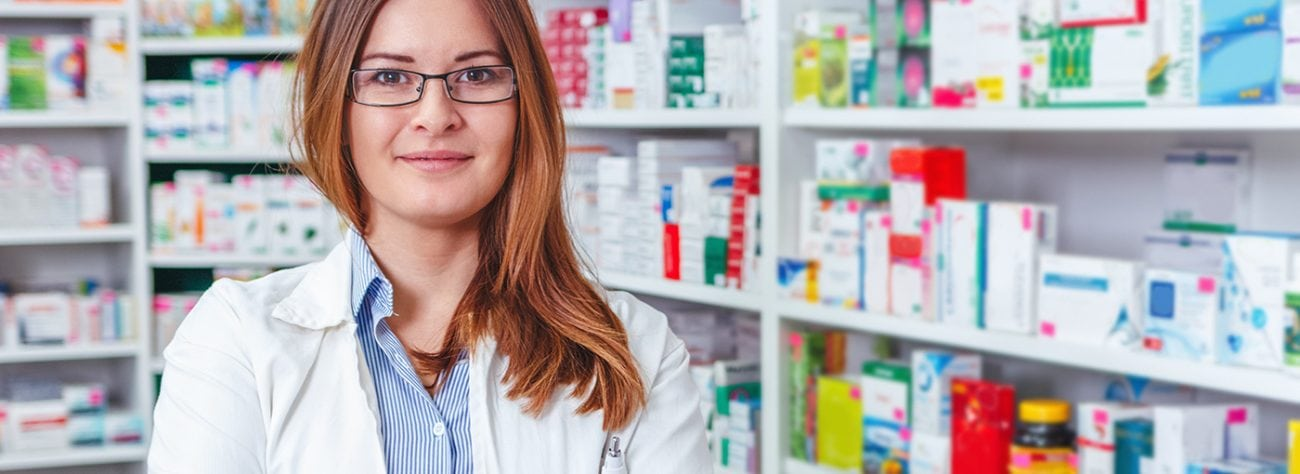 Female pharmacist with red hair looking at camera in pharmacy