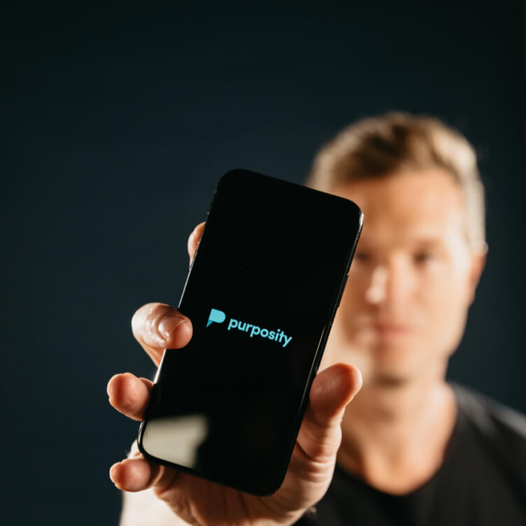 Blake Canterbury holding up a phone displaying the Purposity Logo