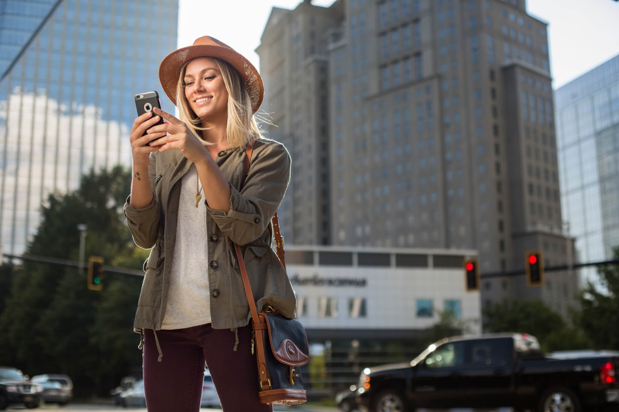 A Woman holds a smart phone with downtown scenery in the background