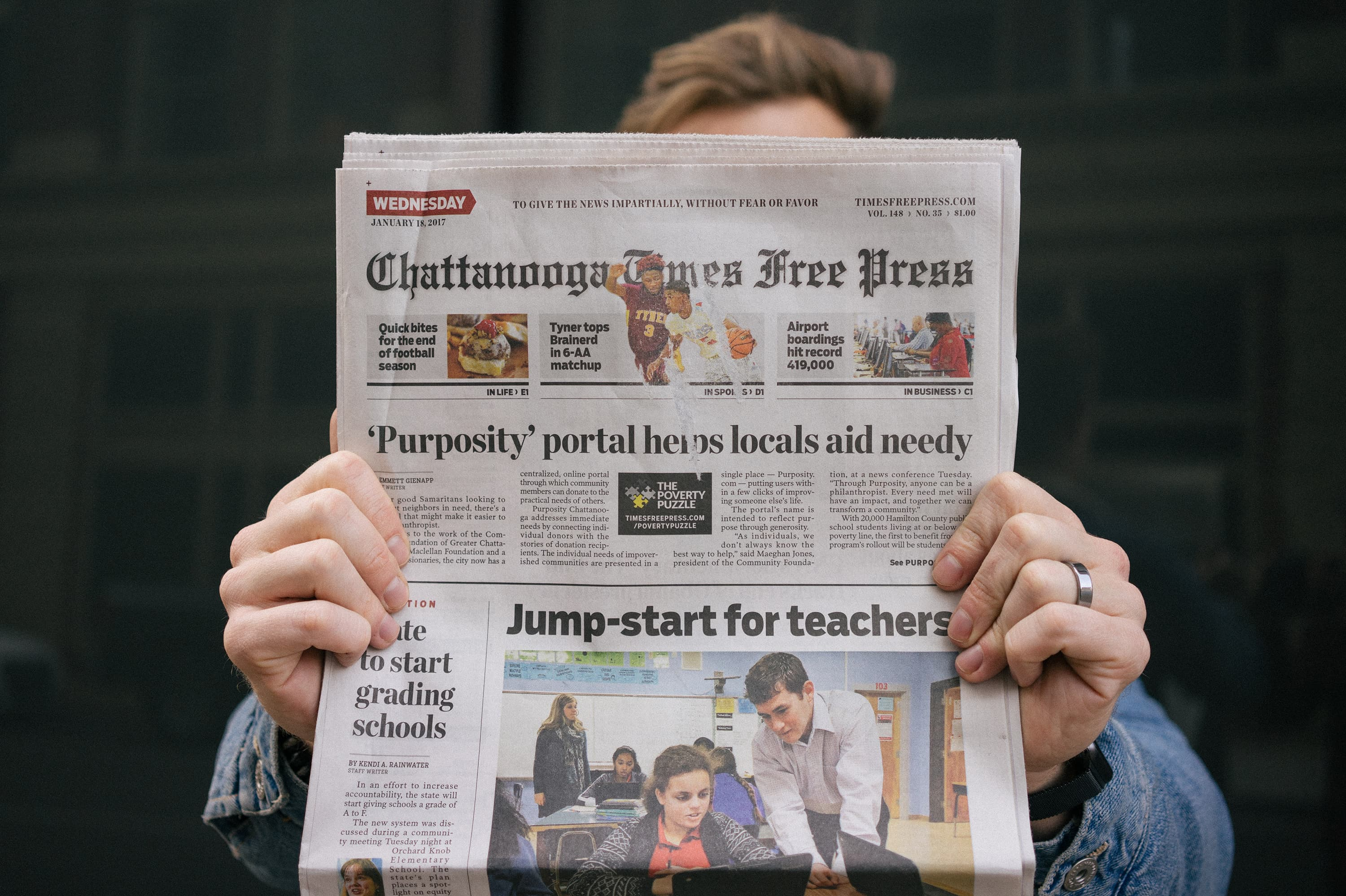 "A man holds up a Chattanooga Times Free Press newspaper showing an article entitle ""Purposity portal helps locals aid needy"""