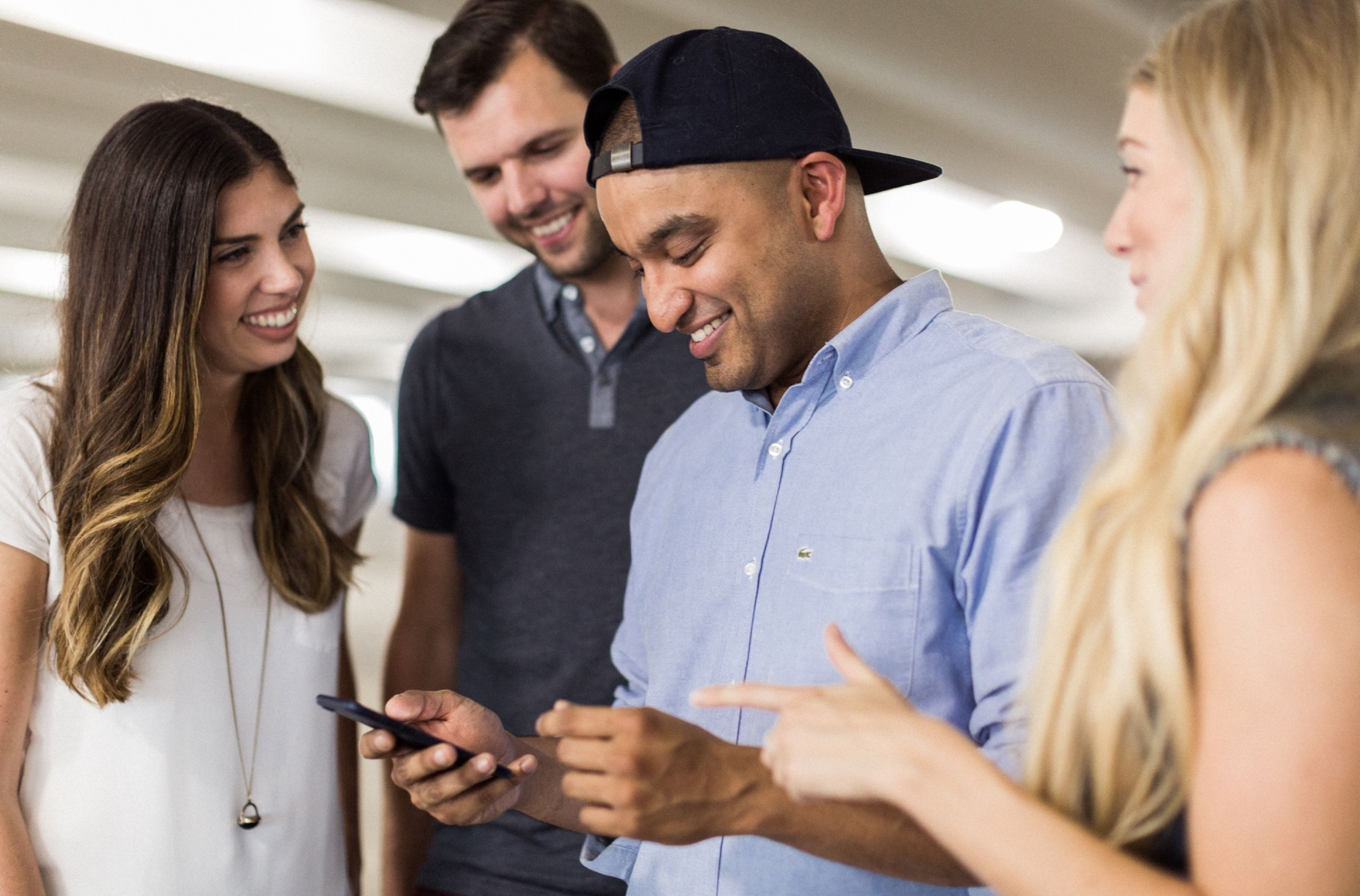 A group of 4 smiling people look on as a man scrolls on a smart phone