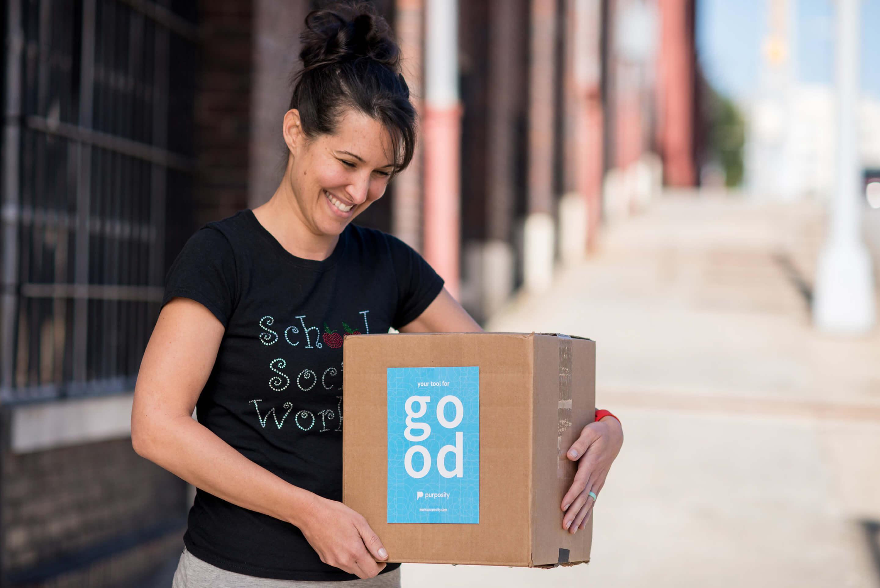 "A woman holds a box with a label on it that reads ""Purposity: Your tool for good"""