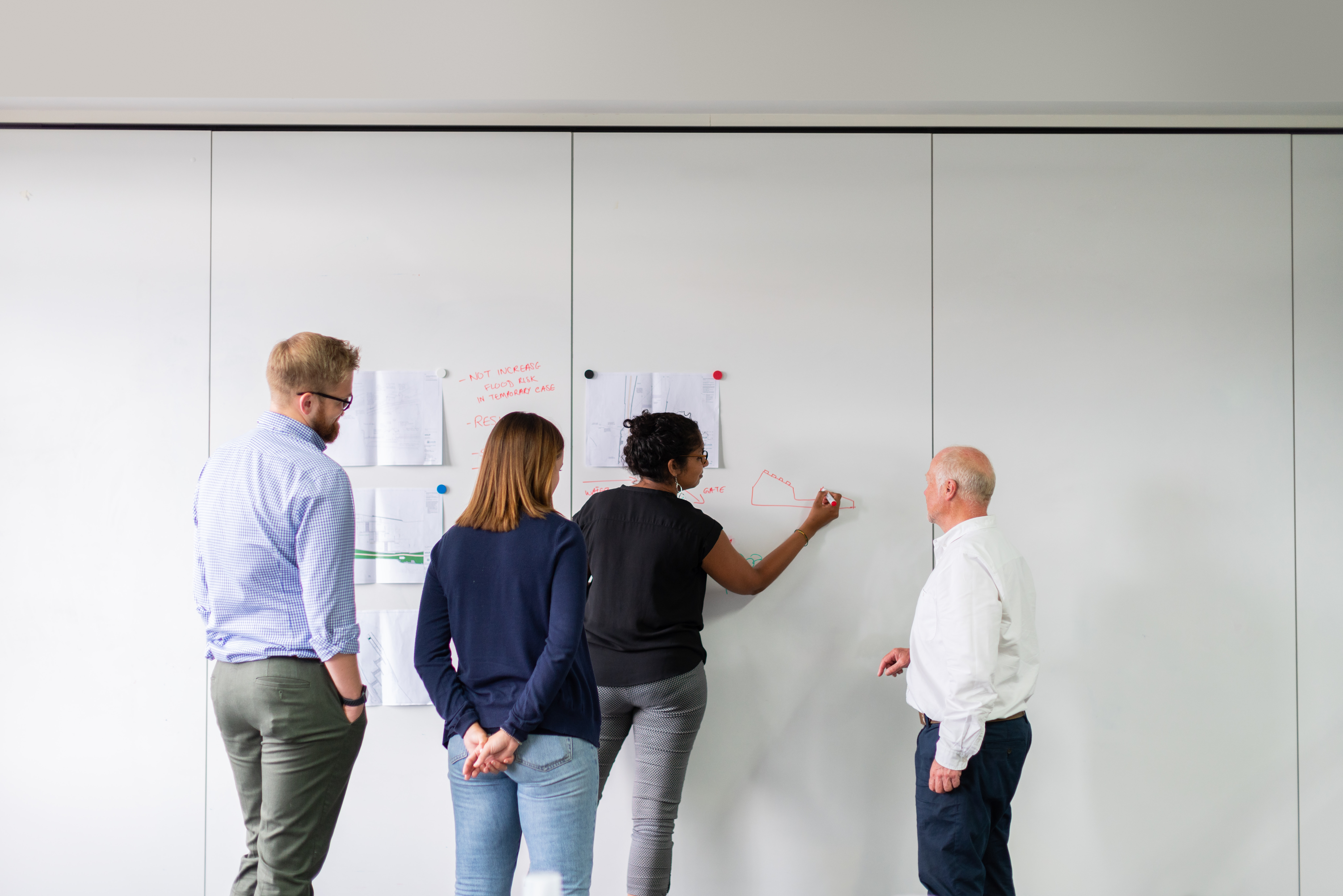 Four employees stand in front of a white board while one of them writes on it.