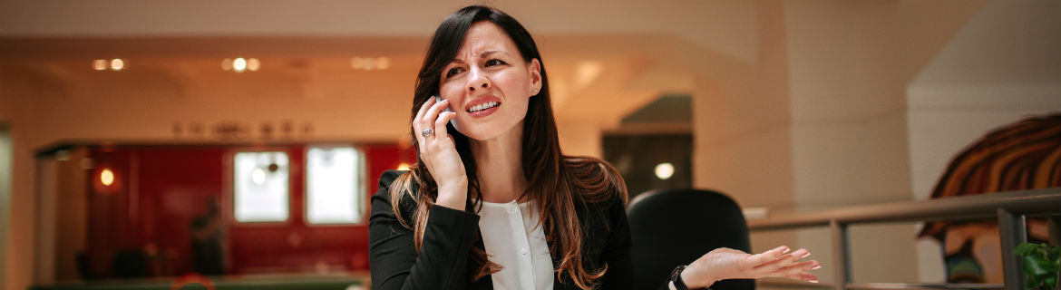 Confused looking woman talking on smartphone in shopping centre