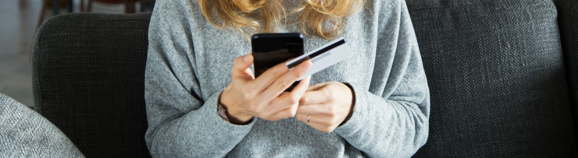 Woman in light grey sweater sitting on a dark grey couch making a purchase with a credit card on her smartphone