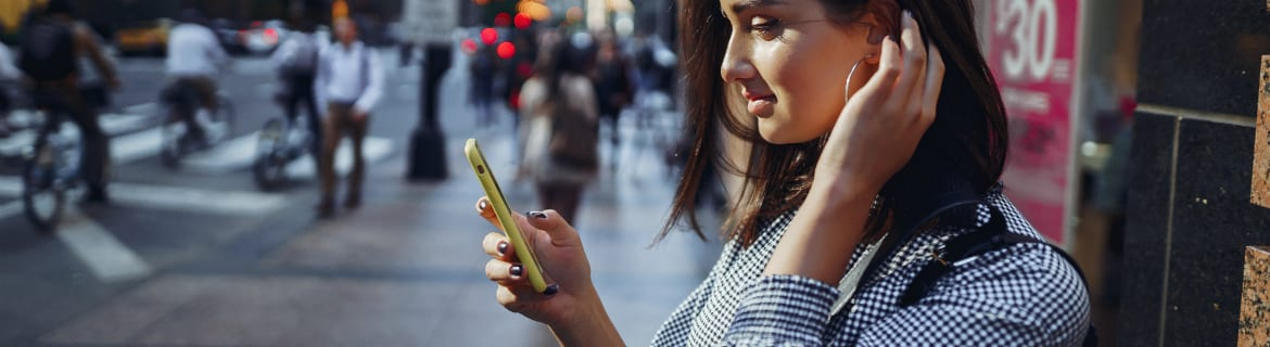 Woman with large hoop earrings looking at smartphone on a city street
