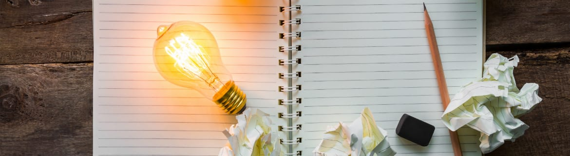 Open notebook with light bulb illuminated next to a pencil with serval pieces of crumpled paper