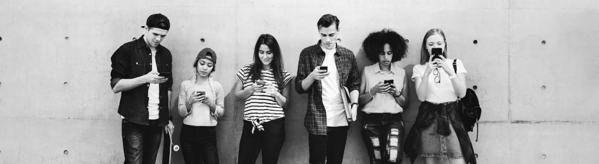 Black and white image of a group of millennials leaning against concrete wall all looking at smartphones