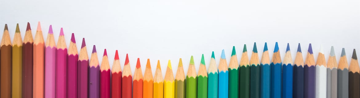 A line up of coloured pencils going through the colours of the rainbow