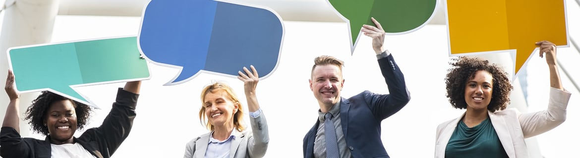 Group of people holding paper cut outs of coloured speech bubbles