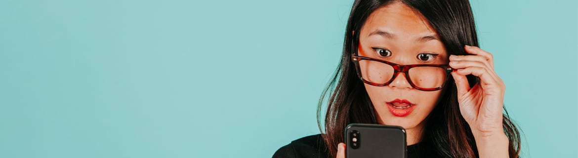 Asian woman pulling down brown glasses with a surprised look on her face looking at a black smartphone in her hand