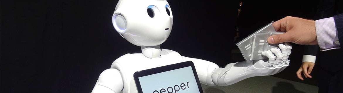 Pepper the robot assistant handing something to a man in a suit